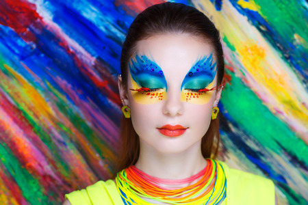 Creative make-up new conceptual idea. blue orange yellow red colors bold body art painting. Crazy graphic abstract picture on woman face surrealistic. concept professional photo. Creativity background