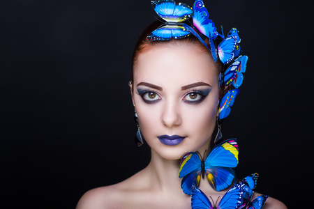 Bright blue butterflies seating on woman head, hair, neck. Oriental beauty girl professional makeup. Portrait of a beautiful lady who wore big accessory. Young fortune teller predicts fate horoscope