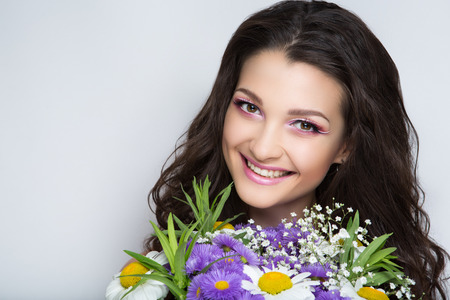 Pretty girl sniffing flowers bouquet. Creative young lady bright makeup brunette hair. Streams of flowers, shiny cheek colored big eyes pink ultra mat lips. Professional photo new stylish florist idea