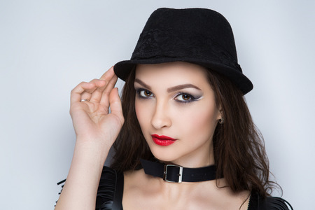 Beautiful woman, necklace choker leather belt, stylish hat. Long hair brunette. Professional cosmetics makeup. Red matte lipstick lip-gloss. New photo close portrait, gray color background horizontal