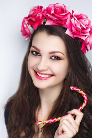 Young beautiful girl with a fashionable hairdo and professional makeup. Gold glitters shadows, perfect shape lips, tender shiny lips-gloss color lipstick. Luxury accessory big flower wreath, lollipop
