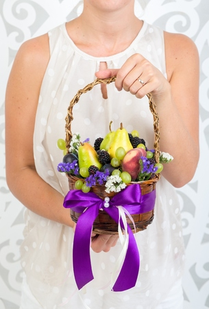 Big wicker basket, bouquet of fruits. original unusual edible present. Close up. useful gift for a proper lifestyle. autumn harvesting of fresh grapes, pears, concept of accumulate vitamins for winter