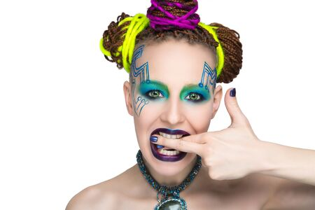 Girl woman creative make-up, lines motherboard painted on her face. Long fingers with manicure. Purple violet lips, eyes lenses, colored blue green shadows. Hair dreadlocks braided, neon yellow string Stock Photo