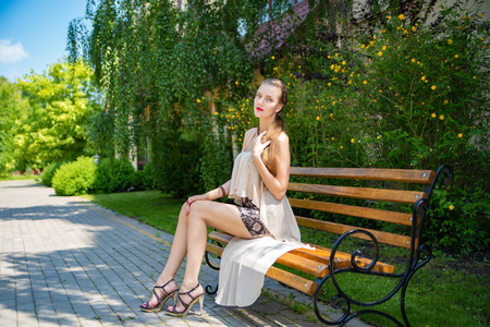 Beautiful girl with very long legs in a short skirt sits on a bench. Skirt is made of python skin, stylish reptile print, transparent silk fabric chiffon drapery. Red lips cosmetics, bright make-up
