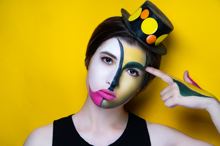 New creative make-up, conceptual idea for Halloween club party. Yellow bold color graphic shapes, cosmetics shadows paints black lines lips. Professional close-up photo. crazy skin painting artistic