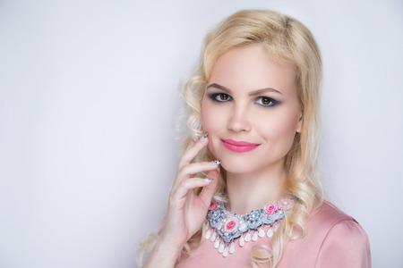 Young glamour girl. Sexy woman, blonde hair-do, pink blouse, crimson lips lip-gloss lipstick.  Fashion blond princess with pink make up, professional manicure. Fingers touch face. Massive jewellery