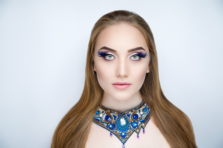 Beautiful woman lady girl with long golden hair, high quality coloring, hairdresser ads, beauty saloon. Banner for advertising shampoo or hair care products. Massive necklace, blue beads gems stones Stock Photo