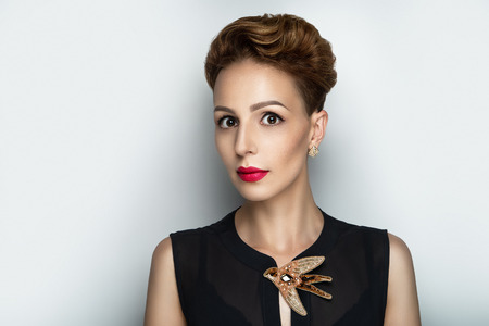 Sexy girl face, studio portrait closeup. Crazy woman with a short creative haircut painted in gold spray. Orange hair dye. Massive jewellry jewelry cute bird made of beads strass rhinestones diamonds