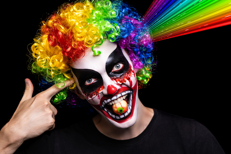 Scary clown make-up for Halloween. Cut skin on cheeks, blood flowing from wounds. Lollipop in the shape of the eye. Horrors of terrible nightmares. Large curly wig rainbow. Bloody mouth painted teeth