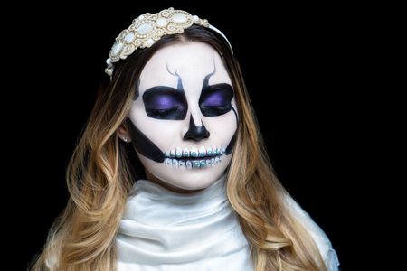 Woman art make up. Scary skull make-up for Halloween. Face-art body-art is painted with paints for body art cosmetics skin. Horror terrible nightmares. Jewelry from beads precious stones. Long hair-do