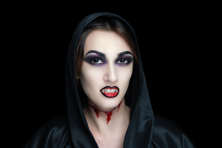 Scary vampire make-up for Halloween. Cut skin on throat, blood flowing from wounds. Black shadows smoky eyes. Horrors of terrible nightmares. Large hood cape woman vamp. Horizontal banner concept idea Фото со стока