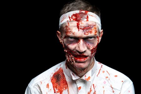 Creative art make-up for Halloween night, man face painted with cosmetics, wounds flowing blood slapping white shirt. Scary zombie. Bandage on his head, turning into a terrible nightmare horror party