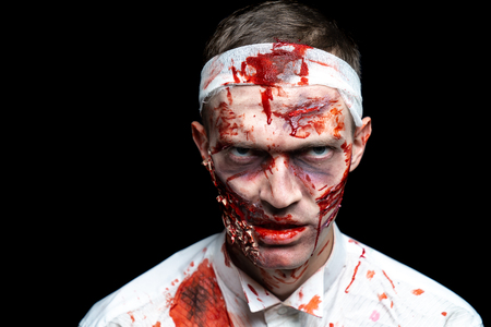 Crazy zombie horror make up. Person in white shirt with bloody sweat. Scars, deep scratches realistic art make-up. head is re-banded bandage, beaten with a stick. Horizontal banner for Halloween party