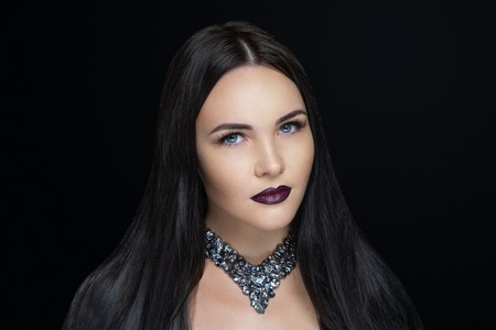 Sexy girl with gorgeous black hair, professional dark makeup. Thick hair hairstyle extensions, dyeing, hair-do care products shampoo. Handmade beads Jewellery, hand-made jewels. New Horizontal banner 免版税图像