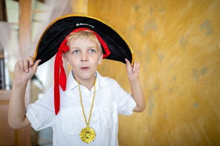 Boy pirate preparing for the holiday Halloween. Big pirate hat captain of a ship, male role play at a costume party children's holiday. Fun and emotions for a good mood. Studio wall horizontal banner Zdjęcie Seryjne
