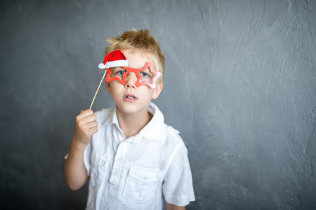 Prepare for the new year party, funny Santa Claus. Beautiful handsome boy with a cardboard eye glasses. Blonde holding a decoration on a wooden stick. Original accessories for photo shoots Imagens