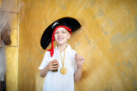 Boy pirate preparing for the holiday Halloween. Big pirate hat captain of a ship, male role play at a costume party children's holiday. Fun and emotions for a good mood. Studio wall horizontal banner