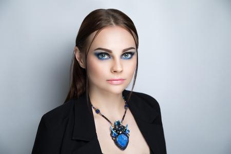 ジャケットを着た若い美少女はセクシーなボディを身に着けていた。髪はしっかりと2本のストランドを解放しました。表現力豊かな夜のメイクアップ青い黒い目スモーキー、口紅、ナチュラルリップベージュリップグロス