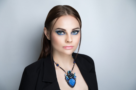 Young beautiful girl in a jacket wore a body sexy. Hair tightly tied two strands released. Expressive evening make-up blue black eyes smokey, lipstick, natural lips beige lip-gloss