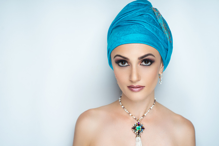 Young beautiful girl wearing blue oriental scarf wrapped around her head. Magic chalma blue ultramarine color. White pearls handmade accessory. Long lashes, new massive necklace, naked sexy shoulders