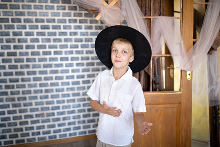 Funny cheerful boy wearing new wizard hat. Handsome guy standing near stone wall in an old castle. Cobwebs abandoned rooms, decorations for the holiday of Halloween, a party on the day of all saints. Stock Photo