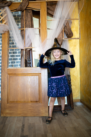 Beautiful sweet girl is preparing for a Halloween party. Baby dressed like a young witch. A blue dress with lace and a black magic hat sorceress cap. Hands on waist, professional model pose. Concept