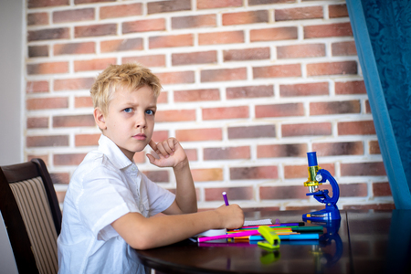 Small boy is sitting at table and crooked, he is surprised, being upset, unhappy. Sprawled stationery markers paper microscope for the study of bacteria. A young scientist is sitting at school room