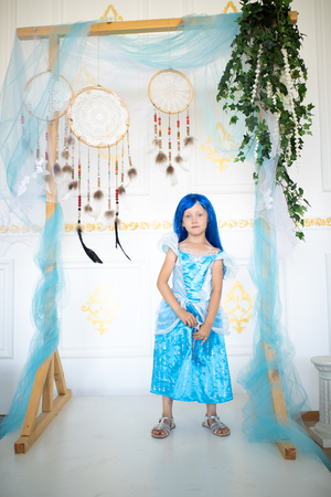 Beautiful little girl in a blue wig. Long hair with bangs. Beautiful evening dress for a costume party for Halloween. Pretty fairy conjures and fantasizes, a magic sorceress. Fun Entertainment enjoy