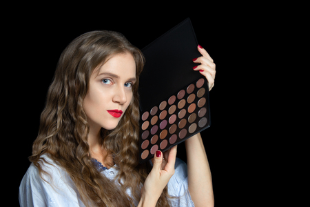 Young beautiful girl holding plastic palette with multi-colored shadows. Brown colors to create customer ideas. Ready to work make-up artist at party or saloon. In the hand of professional tools art Foto de archivo