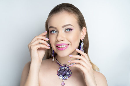 Beautiful woman close up portrait. White teeth smile. Perfect face model. Professional make up - pink eyeshadows, long lashes. Elegant jewelry accessory necklace and ear rings. Tender touch fingers
