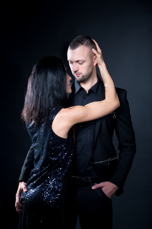 Lovers man and woman are preparing for role-playing games. Dominate obey undress seduce a partner. Girl dressed in black dress. Gentle arms hug around his neck. Sensual date idea. Thematic bdsm party