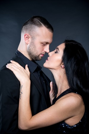 Lovers man and woman are preparing for role-playing games. Nose to nose close hug with partner. Girl dressed in black dress, boss formal suit. Sensual date idea vertical banner. Thematic bdsm party Stock fotó