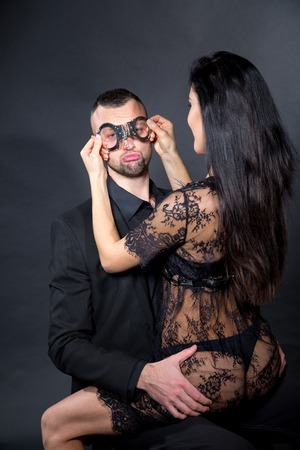 Lovers role-playing games. Girl dressed in black lacy negligee, wearing sexy underwear. Impotence problem, emotional sad. Dominate obey undress seduce a partner. Sensual date idea. Thematic bdsm party Stock fotó