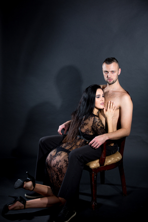Lovers role-playing games. Girl dressed in black lacy negligee, wearing sexy underwear. kneel, caress, trying to excite. Dominate obey undress seduce a partner. Sensual date idea. Thematic bdsm party
