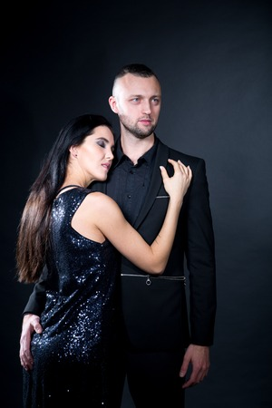 Lovers man and woman are preparing for role-playing games. Dominate obey undress seduce partner. Girl dressed in black dress. Sensual date idea. Thematic bdsm party. Vertical banner professional photo