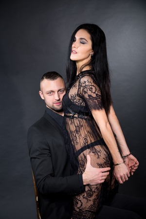 Lovers role-playing games. Girl dressed in black lacy negligee, wearing sexy underwear. Impotence or potency treatment. Dominate obey undress seduce a partner. Sensual date idea. Thematic bdsm party