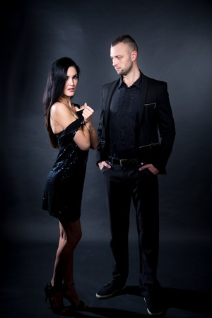 Lovers man and woman are preparing for role-playing games. Dominate obey undress seduce a partner. Girl dressed in black dress, standing sexual pose seduction. Sensual date idea. Thematic bdsm party Stock fotó