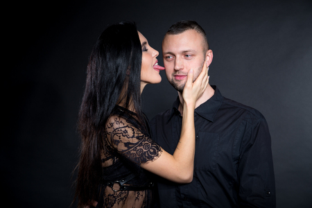 Lovers role-playing games. Girl dressed in black lacy negligee, wearing sexy underwear. Lick boss by long tongue licking. Dominate obey undress seduce a partner. Sensual date idea. Thematic bdsm party 免版税图像