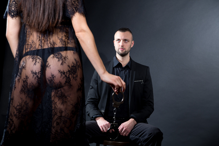 Lovers role-playing games. Girl dressed in black lacy negligee, wearing sexy underwear thong panties, lace mesh, handcuffs. Dominate obey undress seduce partner. Sensual date idea. Thematic bdsm party