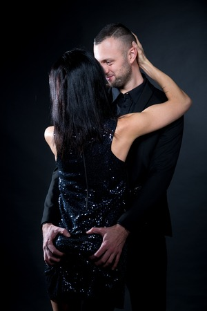 Lovers man and woman are preparing for role-playing games. Dominate obey undress seduce a partner. Girl dressed in black dress, man wearing business formal suit. Sensual date idea. Thematic bdsm party