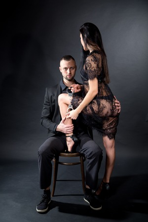 Lovers role-playing games. Girl dressed black lacy negligee, wearing underwear, Puts her foot in high heel shoe between his legs. Dominate obey undress seduce a partner. Sensual date idea