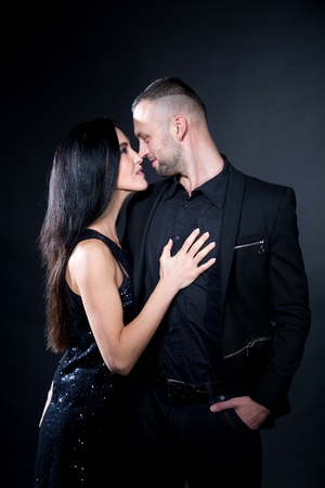 Lovers man and woman are preparing for role-playing games. Dominate obey seduce a partner. Business suit formal. Girl dressed in black dress, wearing sexy skirt. Sensual date idea. Thematic bdsm party