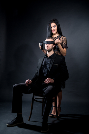 Lovers role-playing games. Girl dressed in black lacy negligee, wearing sexy underwear. Dominate obey undress seduce a partner, boss seating on chair blindfold. Sensual date idea. Thematic bdsm party