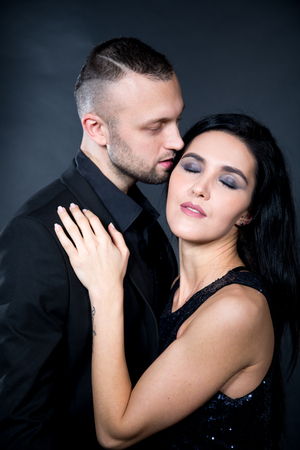 Lovers role-playing games. Dominate obey undress seduce a partner. Girl dressed in black shiny dress. Close whisper from ear to ear. Feel tingles ASMR effect. Sensual date idea. Thematic bdsm party Imagens
