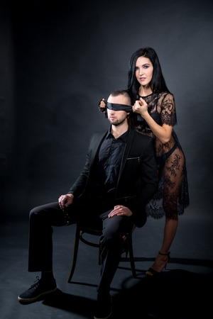 Lovers role-playing games. Dominate obey undress seduce partner, new surprise. She dressed in lacy negligee, he wearing formal style suit blindfolded slave. Wife husband date idea. Thematic bdsm party Foto de archivo - 118132968