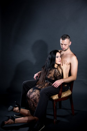 Lovers role-playing games. Dominate obey undress seduce partner, new surprise. She dressed in lacy negligee, he wearing formal style trousers. Wife husband deep night date idea. Thematic bdsm party 版權商用圖片