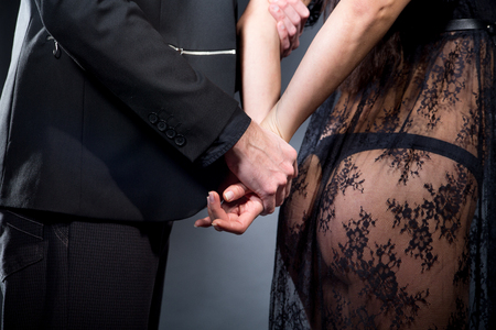Lovers role-playing games. Dominate obey undress seduce partner, new surprise. She dressed in lacy negligee, he wearing formal style suit, catch his victim. Wife husband date idea. Thematic bdsm party Stock Photo