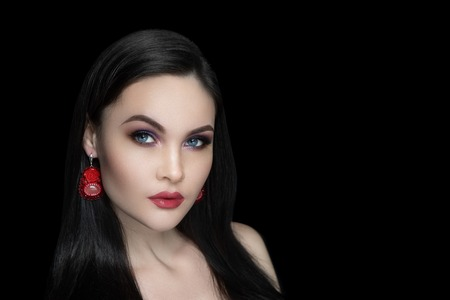 Beautiful woman close up portrait. Professional make up: glossy eyeshadows arrows, long lashes glitters, red colour lipstick lip gloss. Elegant hair, massive flower beads design earrings, naked body Banque d'images