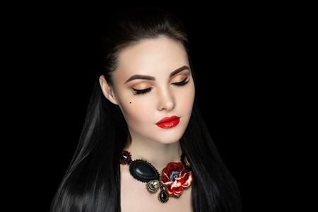Beautiful woman close up portrait. Professional make up: glossy golden eyeshadows, arrows, long lashes beige glitters, red colour lipstick lip gloss. Elegant hair, massive flower beads design necklace Banque d'images