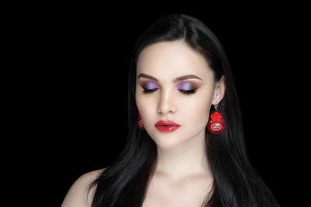 Beautiful woman close up portrait. Professional make up: glossy violet eyeshadows arrows, long lashes glitters, red colour lipstick lip gloss. Elegant hair, massive flower design earrings, naked body